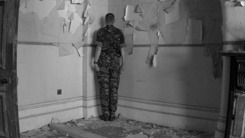 Santiago Sierra, film still from VETERANS OF THE WARS OF AFGHANISTAN, IRAQ AND NORTHERN IRELAND FACING THE CORNER, 2013, Courtesy Estudio Santiago Sierra, Madrid and KOW, Berlin